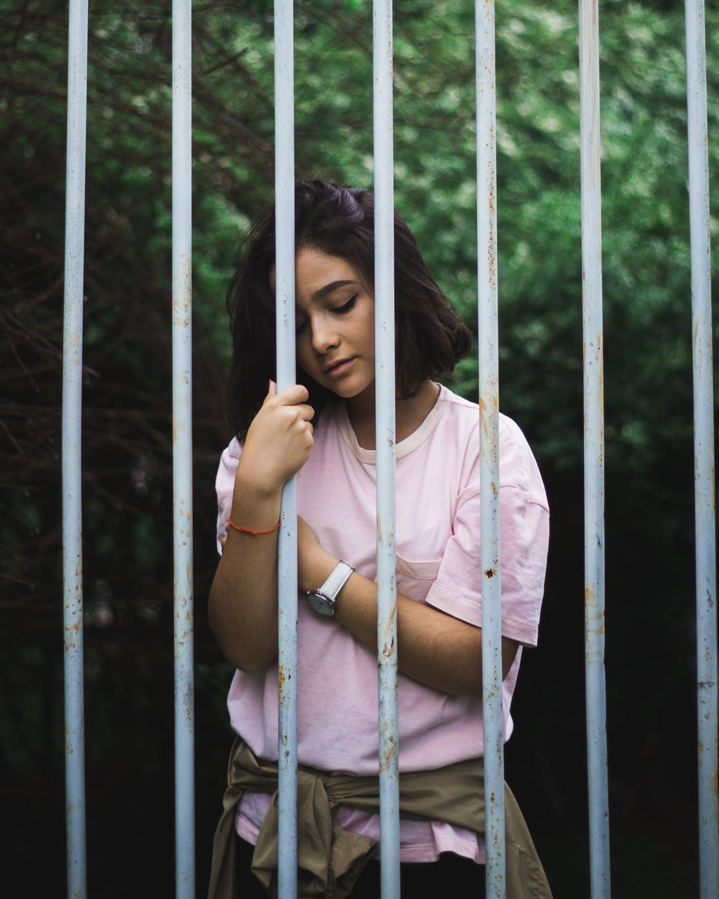 woman wearing pink crew neck t shirt standing and leaning behind white bars
